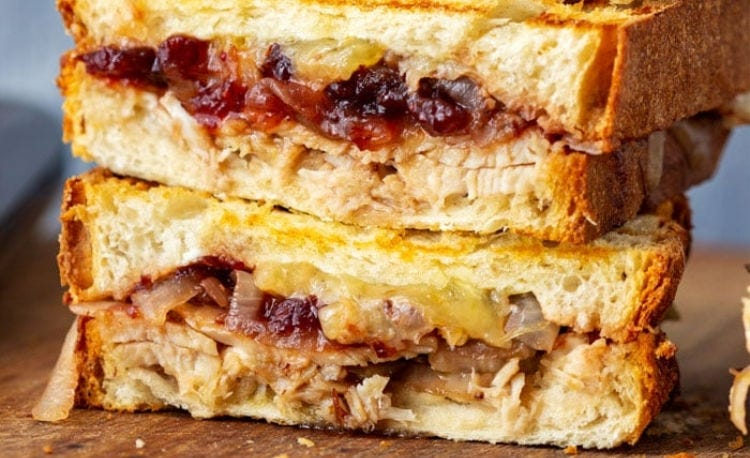A panini sandwich filled with cheese, caramelized onion, turkey and cranberry sauce.