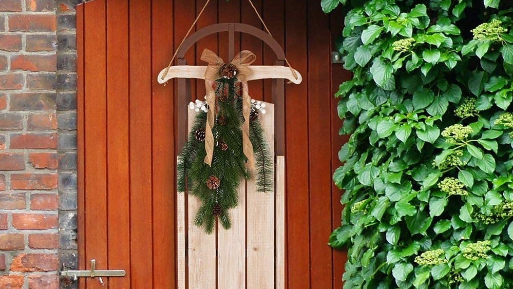 Decorative sled hanging on a door.