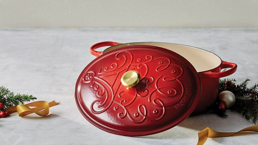 A red dutch oven with a swirling pattern on the lid sits on a marble countertop.