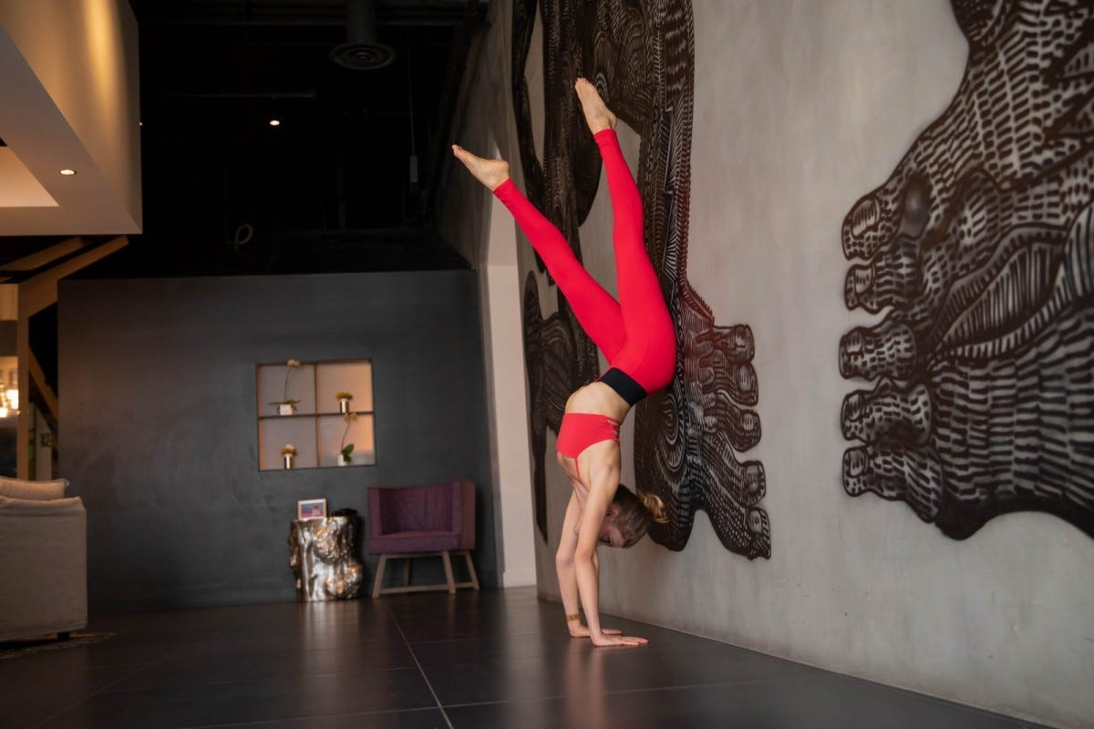 Woman wearing red in handstand
