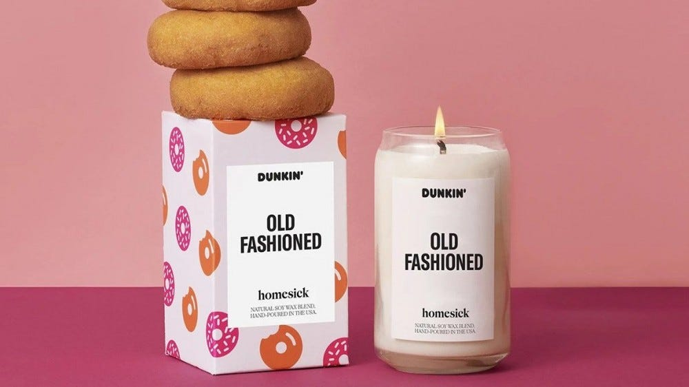 A doughnut-scented candle sits on a counter with doughnuts stacked on top.