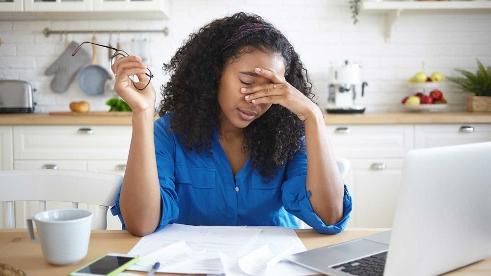 A woman looking exhausted while working from home at the kitchen table.