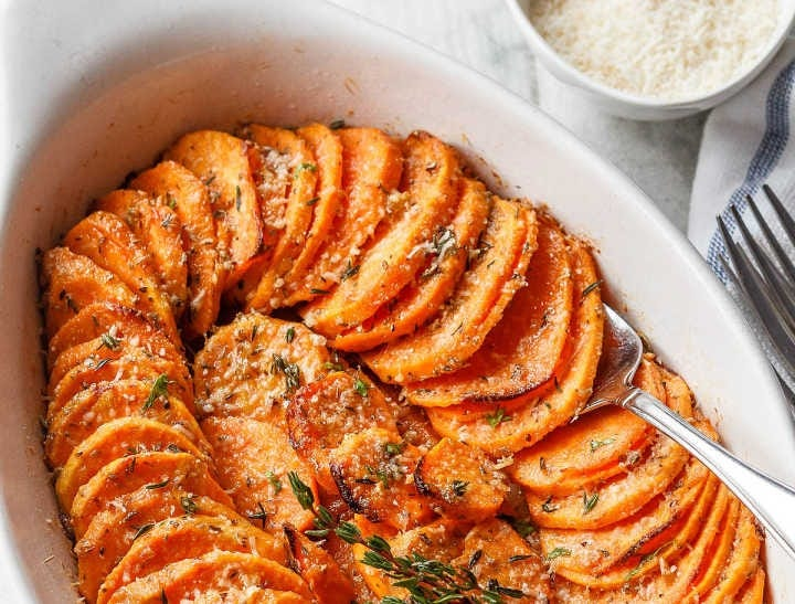 An oven casserole with arranged sweet potato slices that are covered in Parmesan, garlic and other ingredients.