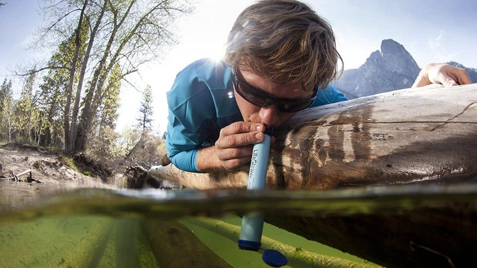 A man drinking water from a ravine in the woods through a LifeStraw.