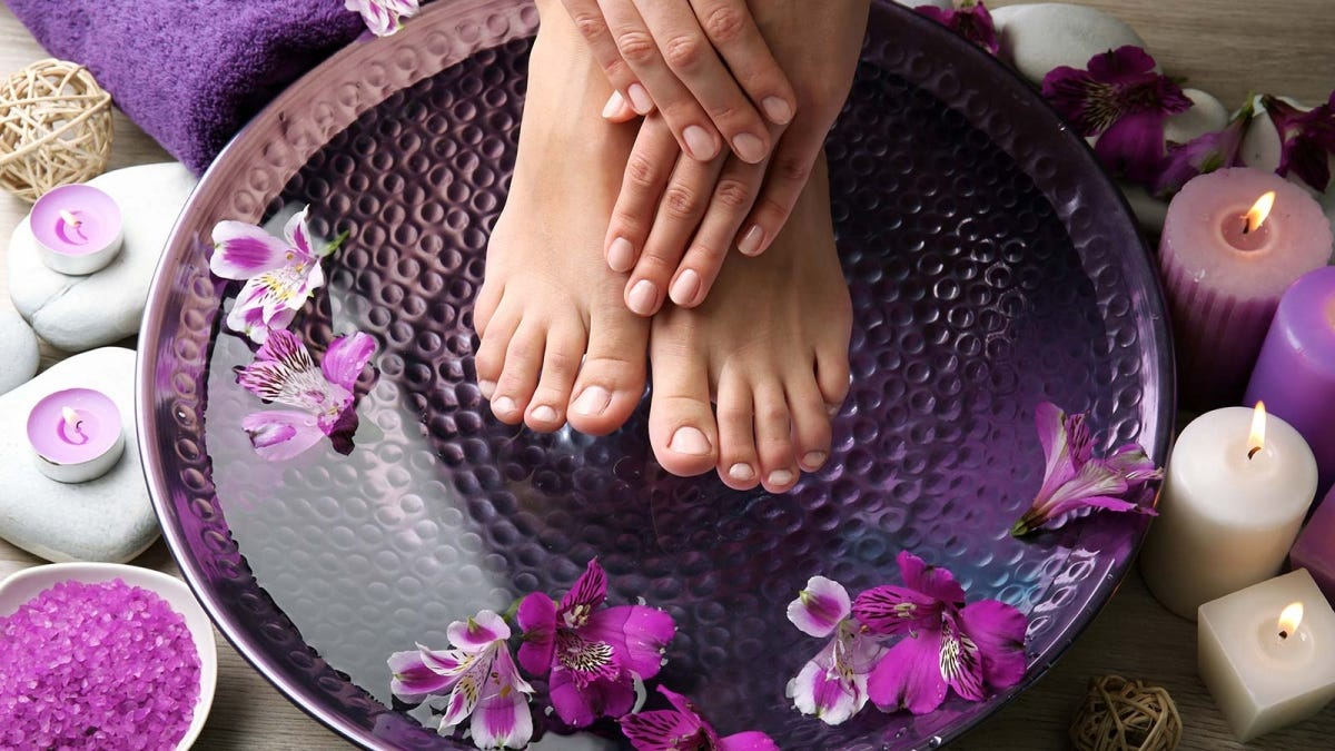 Woman putting her feet into a bowl of warm water, surrounded by candles and flowers.