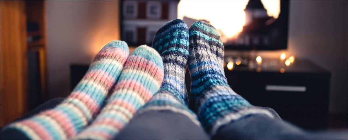 Couple with socks and woolen stockings watching movies or series on tv in winter.