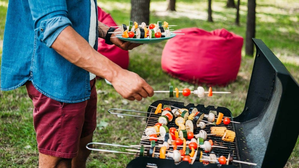 A man placing skewered vegetables on a grill.