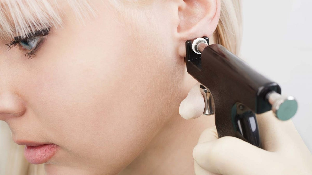 Woman getting her ears pierced by someone using a piercing gun.