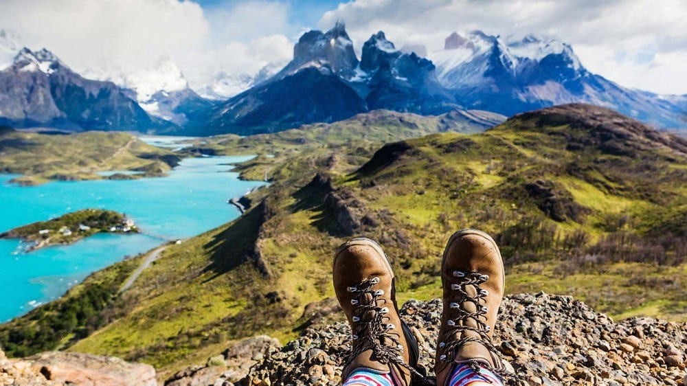 A pair of hiking boots with mountain range and river on the horizon.