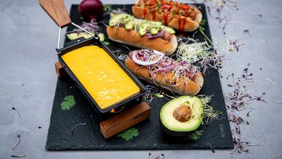 The Bosca cheese melting tray full of cheese and sitting next to three hot dogs covered with the works.