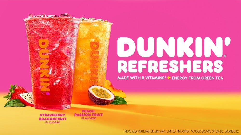 Two Dunkin Doughnuts Refresher drinks sit in front of a pink and peach background.