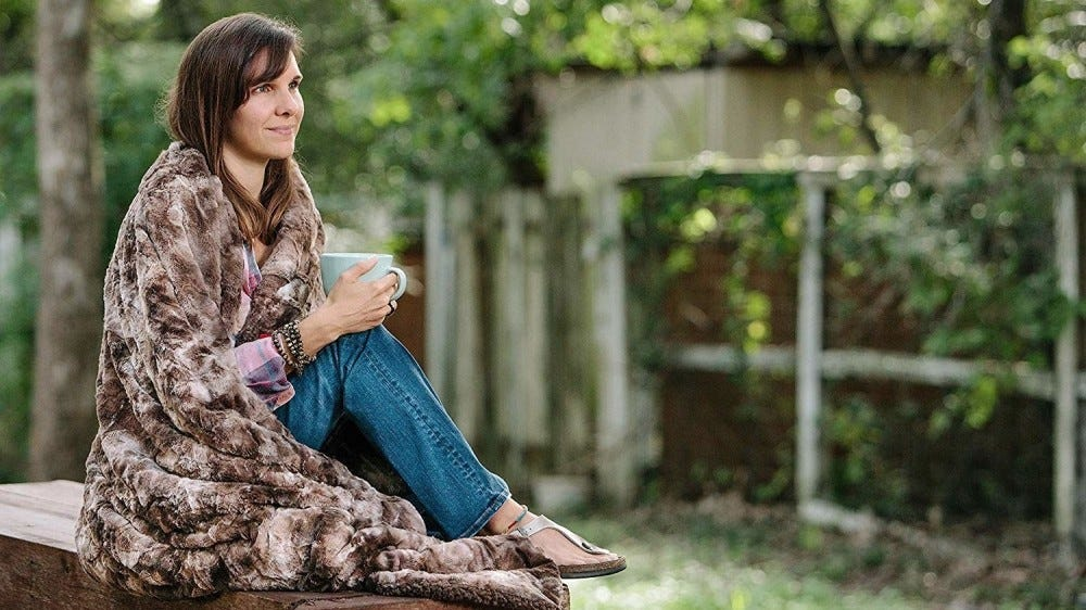 A woman sits on an outdoor bench wrapped in a faux fur throw blanket.