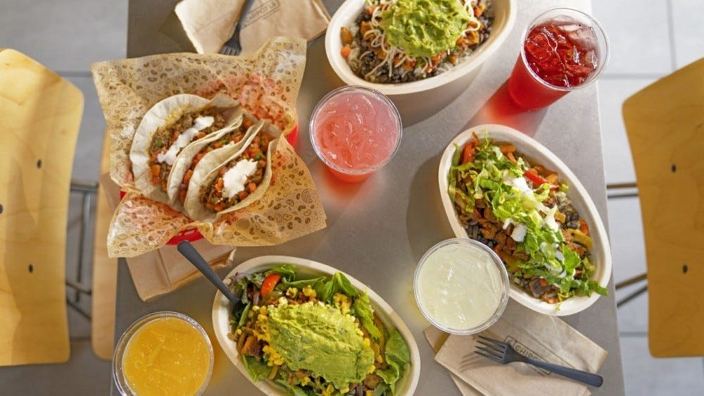 Chipotle burrito bowls and tacos sit on a table with lemonades