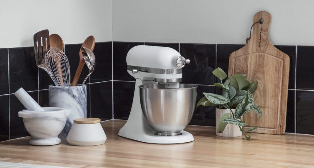 A white stand mixer sitting on a wooden countertop.