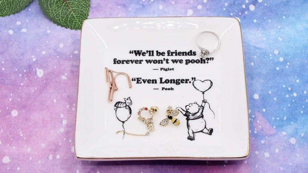 A Winnie the Pooh dish with pieces of jewelry in it.
