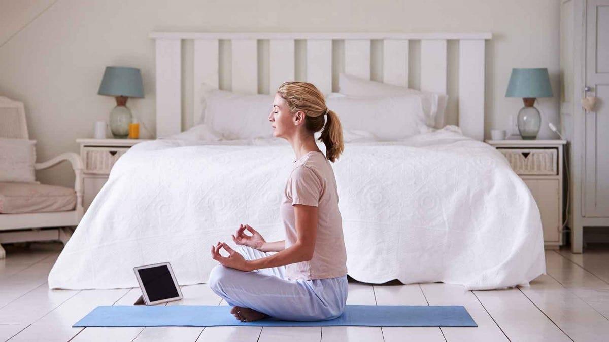 Nő meditál a hálószobájában egy meditációs alkalmazás segítségével az iPadjén