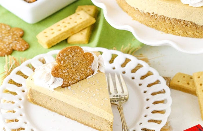 A slice of gingerbread cheesecake with a gingerbread cooking garnish pressed into the cake.