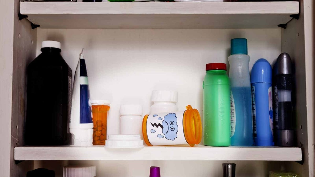 Medicine cabinet shelf with various bottles and tubes, and an empty pill bottle tipped over.