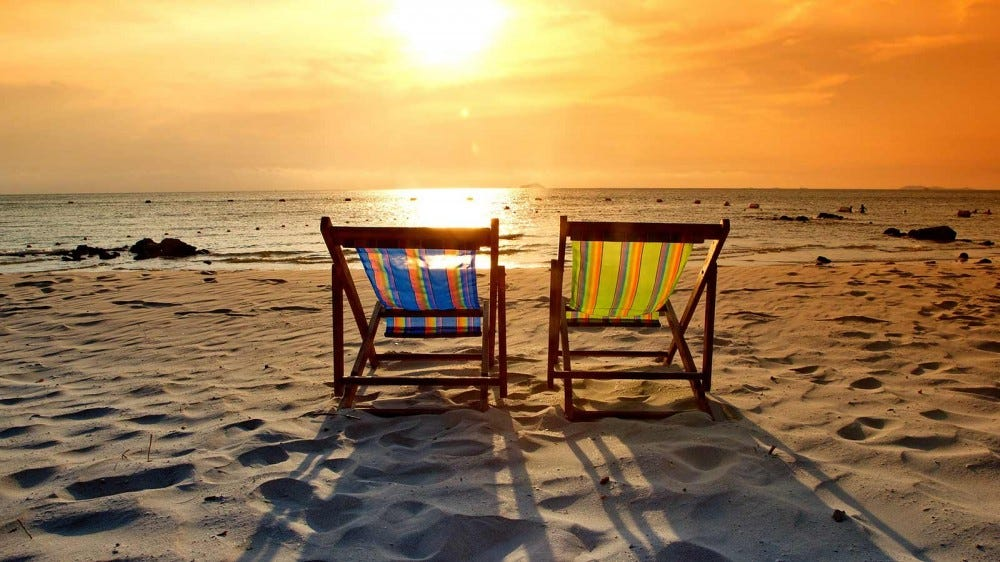 Two empty chairs on a beach at sunset.