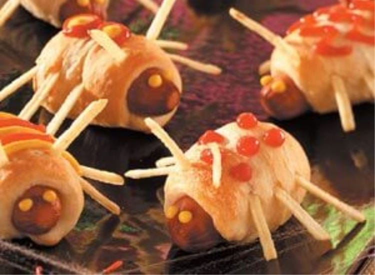 Hot dogs rolled with dough, with potato sticks inserted to look like little edible bugs.