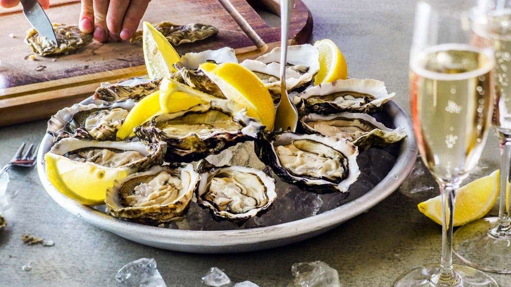 A plate of freshly opened oysters with lemons and a flute of champagne.