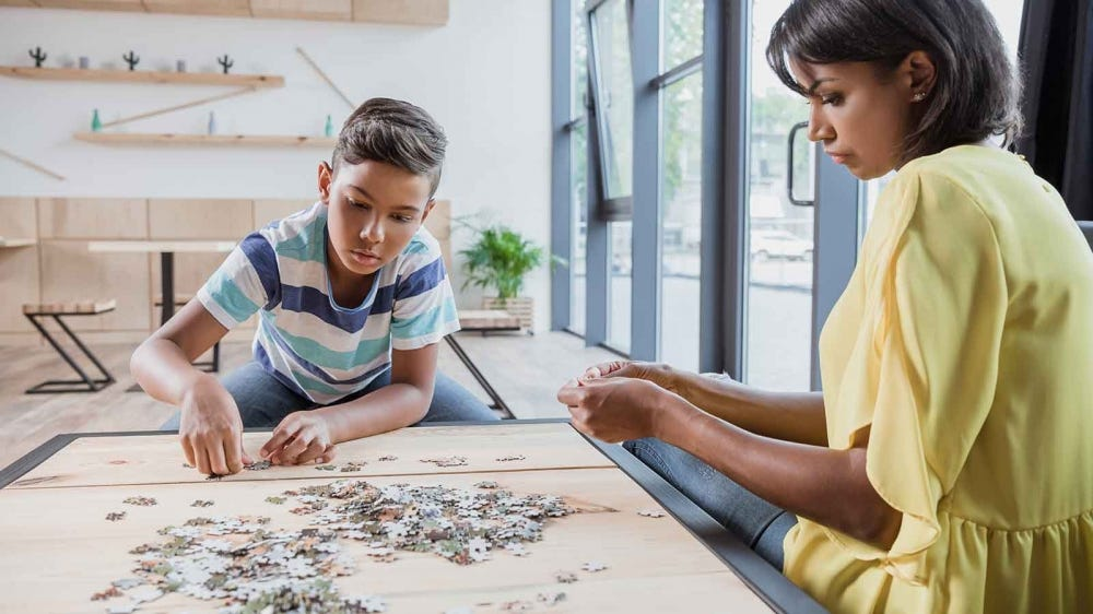 A woman and young boy working on a jigsaw puzzle.