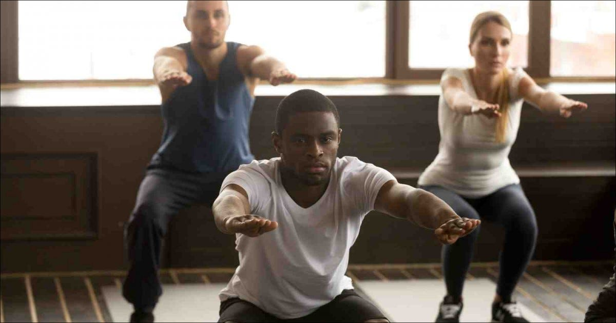 two men and a woman doing light squat exercises in gym
