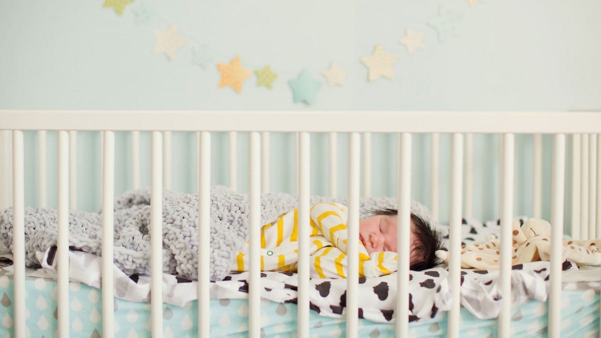 A baby sleeping in a baby bed.