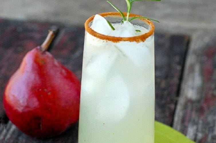A glass full of Ginger Pear Snap sitting next to a pear.