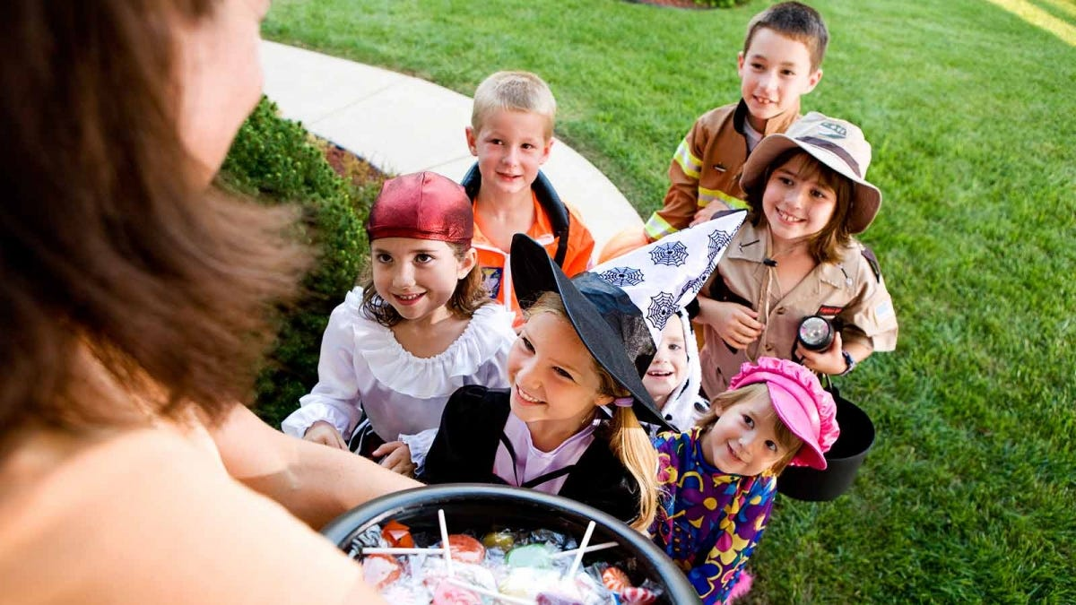 a group of kids trick or treating in a yard
