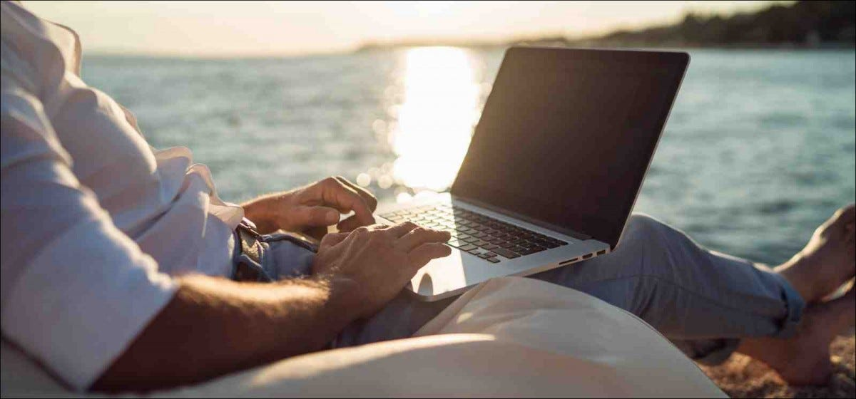 man working on his laptop on the beach during sunset