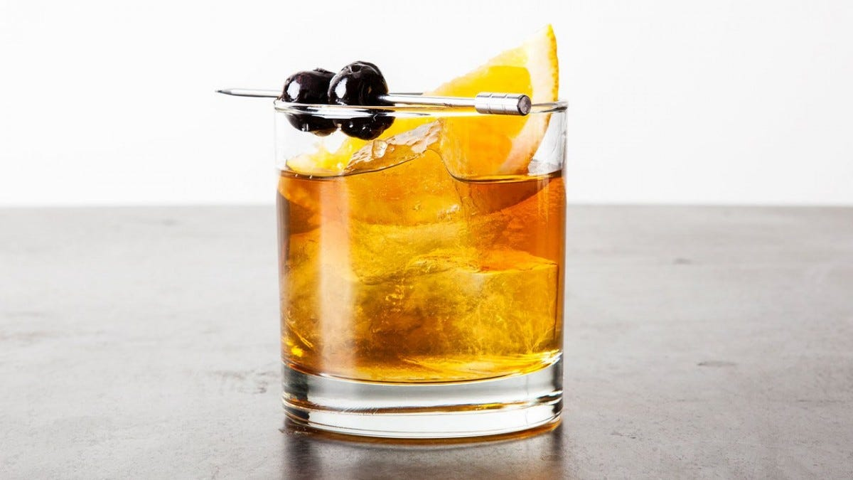 An Old Fashioned in a glass tumbler with two black olives on a spear lying across the top.