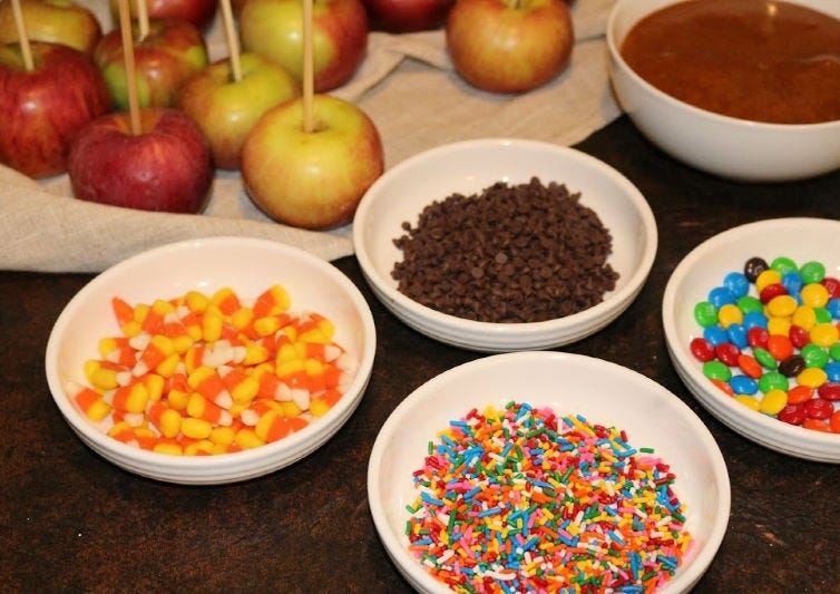Separate bowls of decorative ingredients including sprinkles, candy corn, chocolate chips, and M&M's