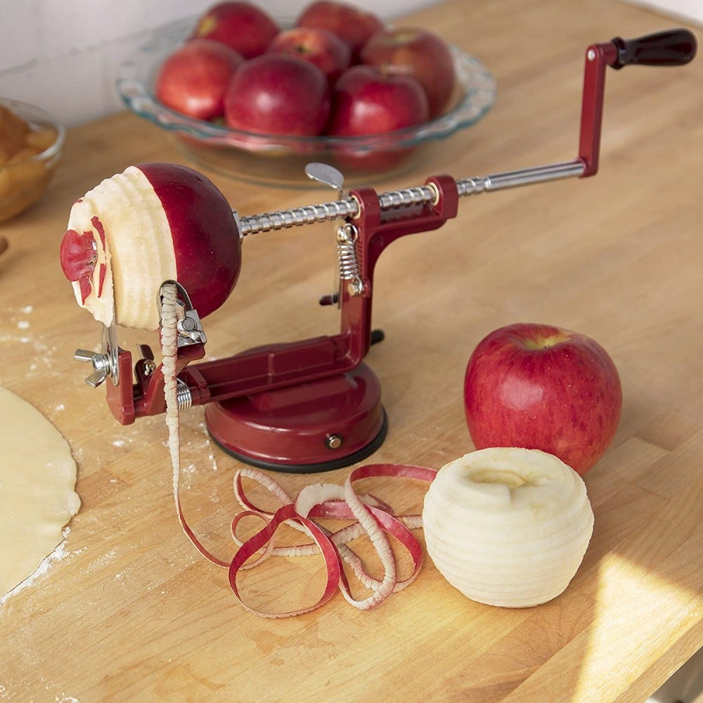 An apple peeling device, attached to a wooden counter, surrounded by apples.