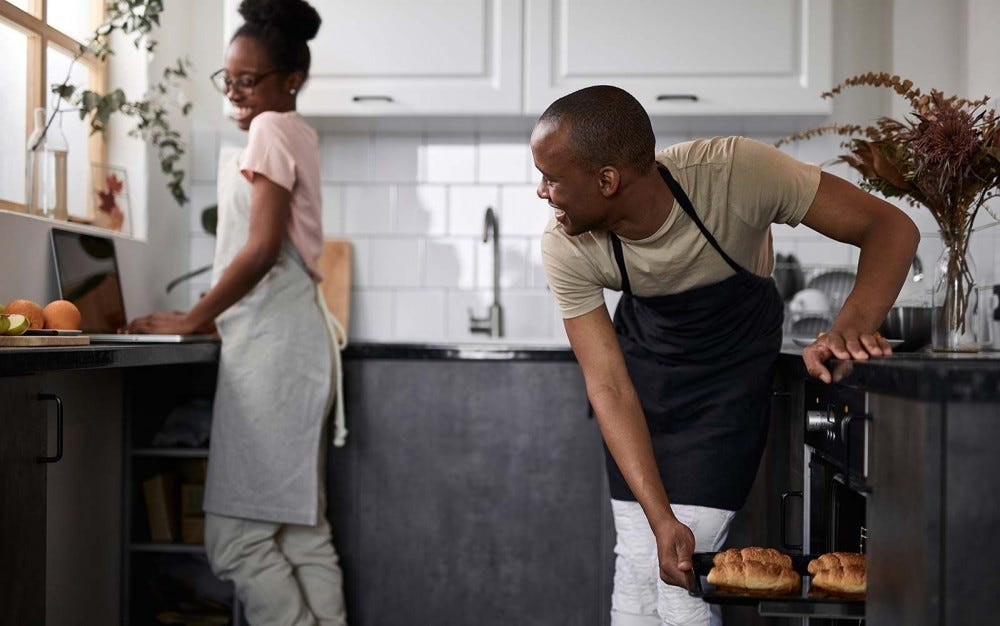 A happy couple baking in the kitchen.