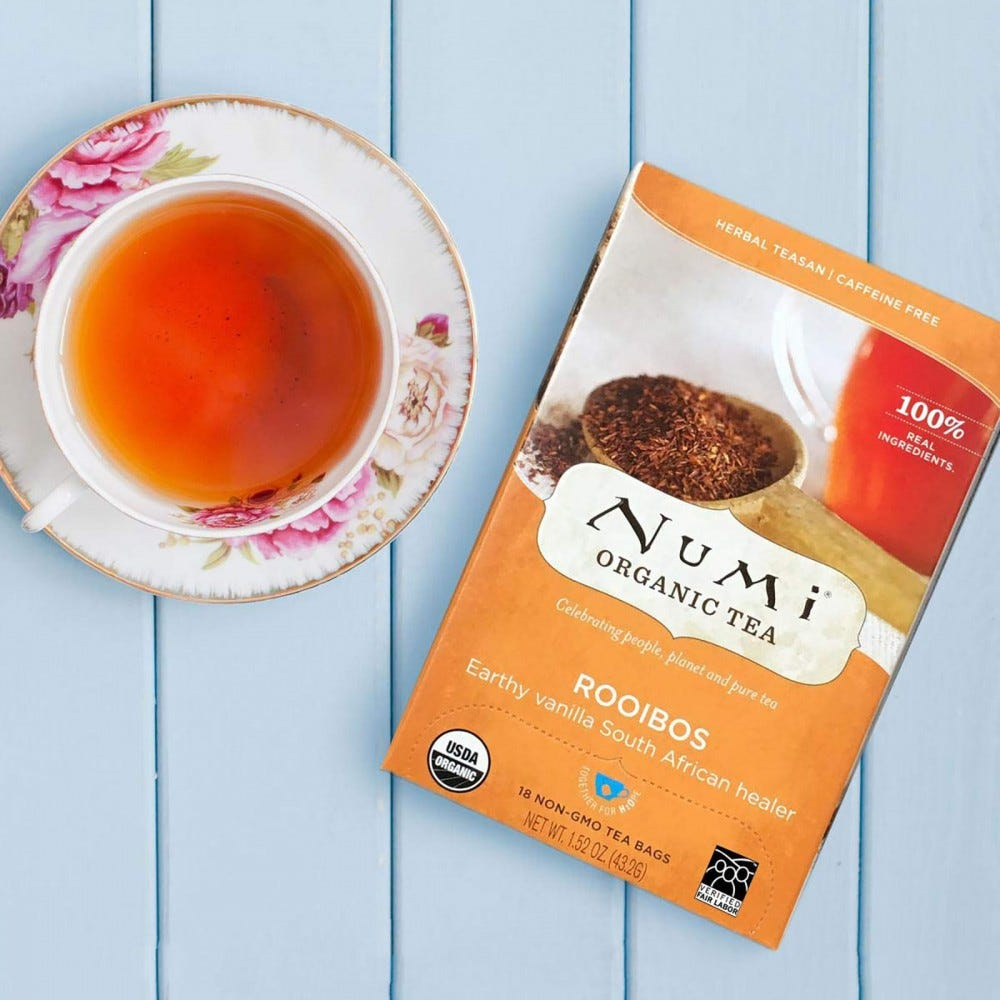 A packet of Numi Rooibos Tea sitting next to a cup filled with it on a saucer.
