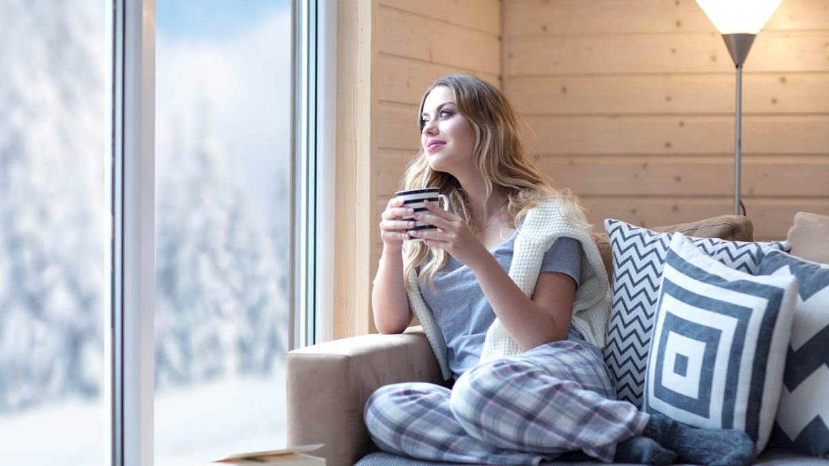 A woman sitting on a couch holding a mug looking out a window at the snow.