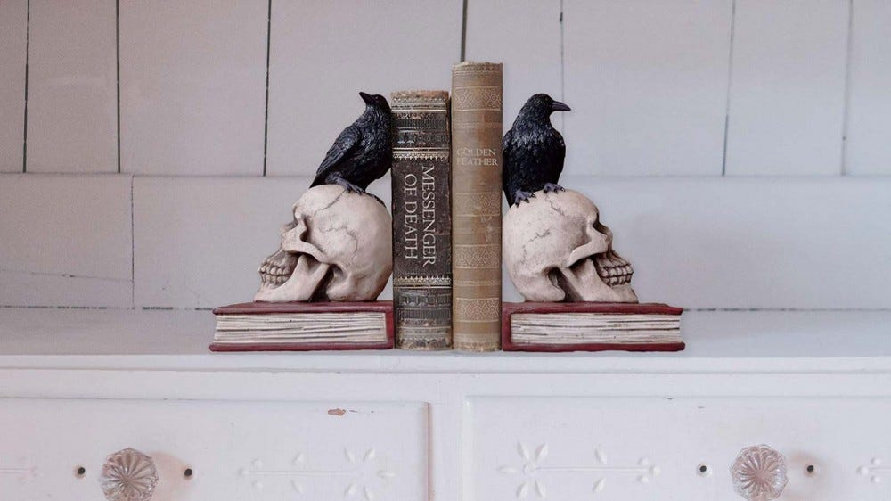 The DWK Murder and Mystery Ravens on Skulls Bookends holding up two Halloween-themed books.