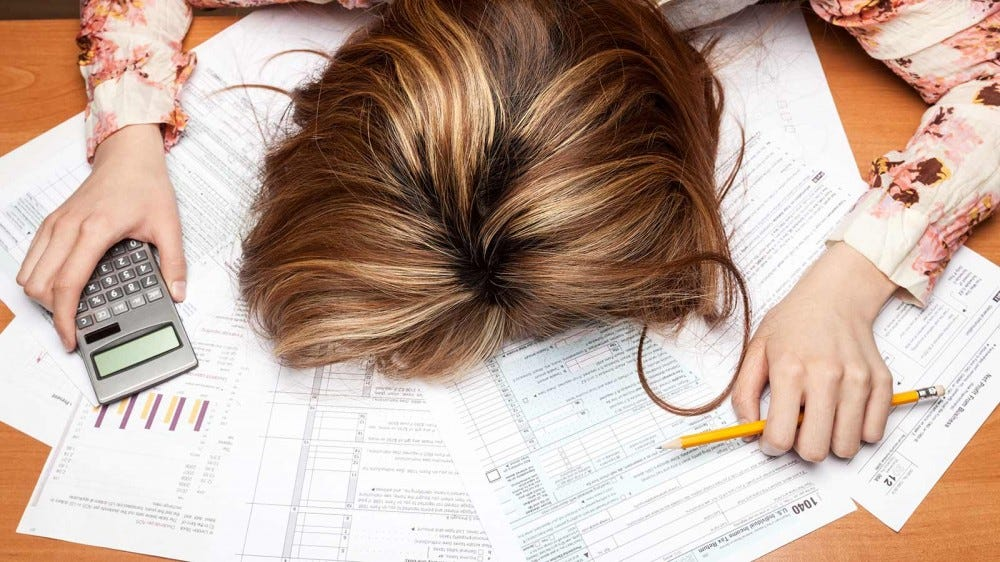A woman face-down on a pile of papers on a desk.