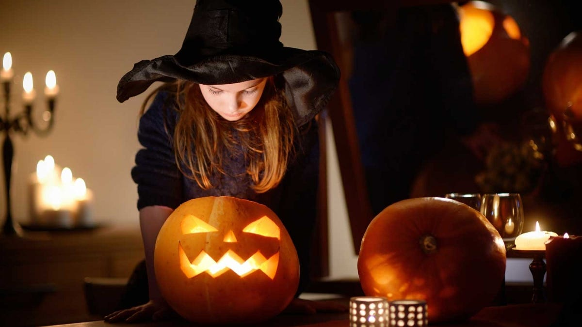 A young girl dressed as a witch looking into a jack o' lantern.