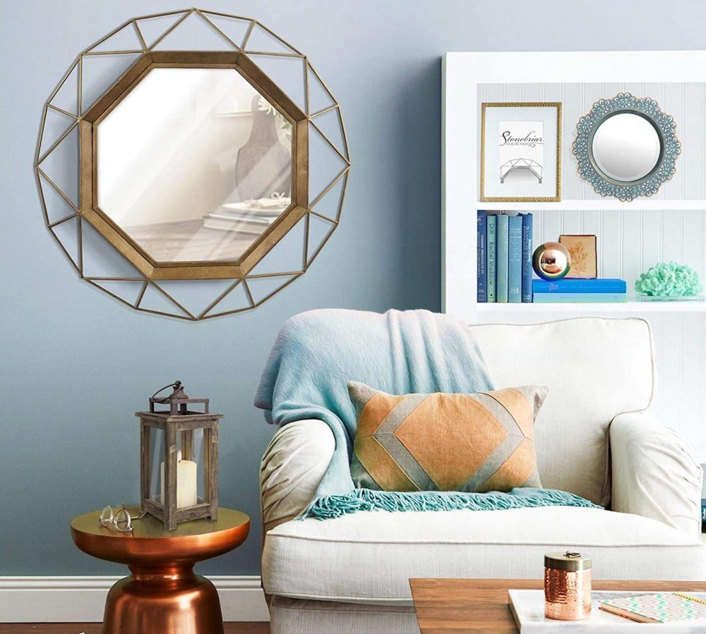 Geometric wall mirror in a living room with a white chair and bookshelf
