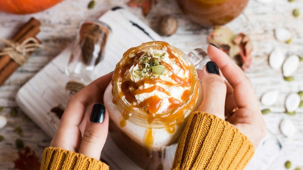 A woman's hands holding a pumpkin spice beverage topped with whipped cream and caramel.