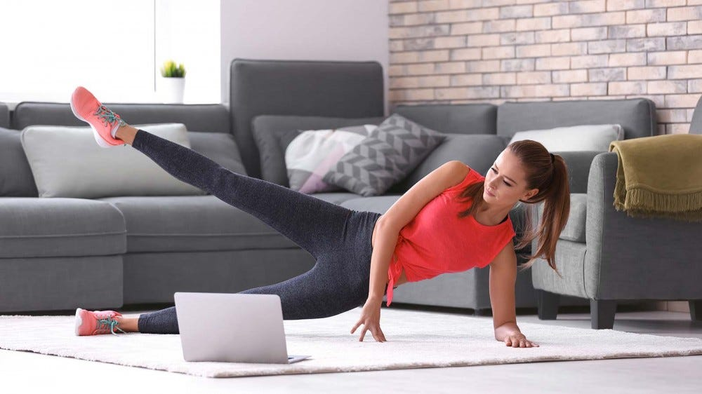 A woman doing an online workout in her living room.
