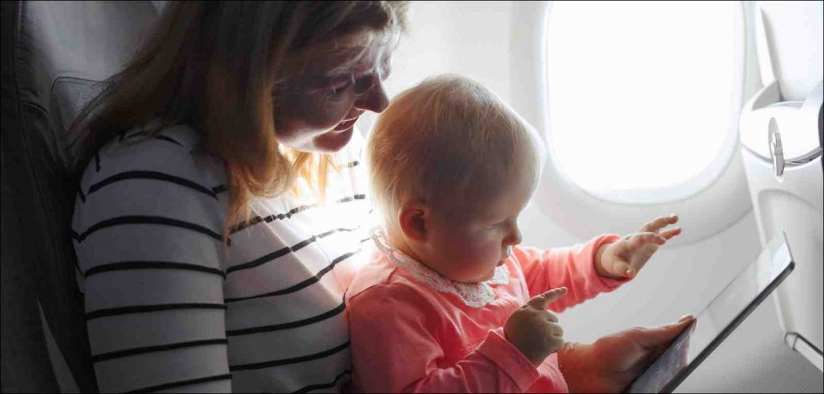Mom and child playing on tablet while flying on plane