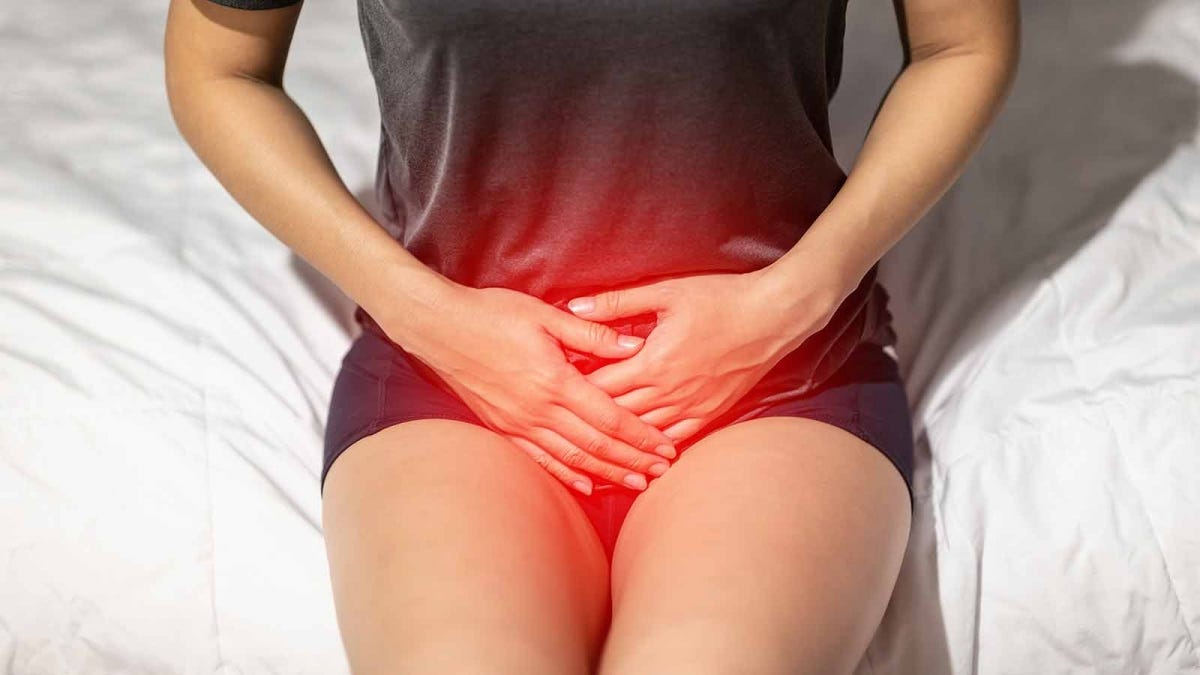 Woman with her hands over her bladder, suffering through the discomfort of a urinary tract infection
