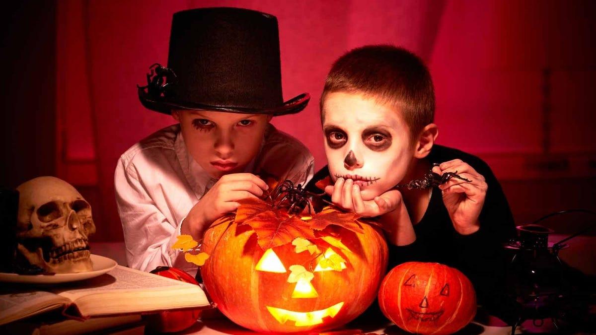 Two boys dressed up for Halloween posing around jack-o'-lanterns and fake skulls.