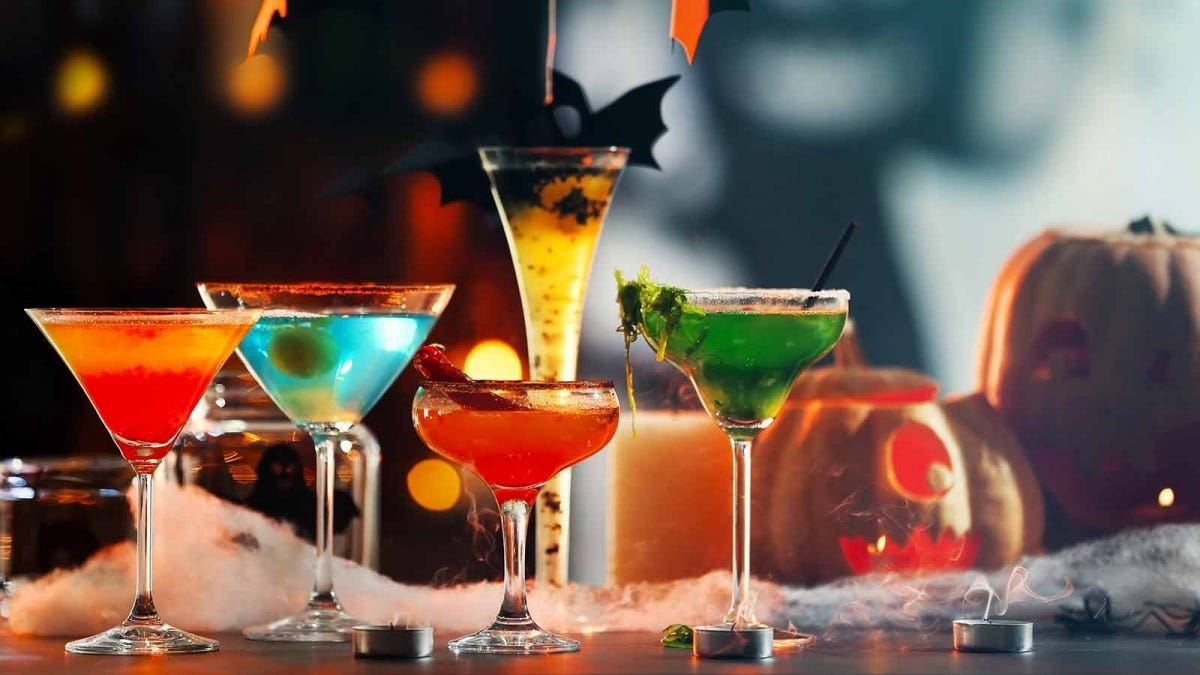 Five cocktails sitting on a table surrounded by Halloween decorations.