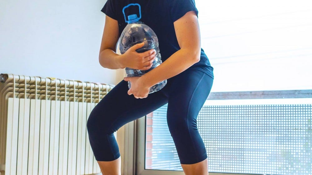 A woman doing squats while holding a one-gallon water jug.