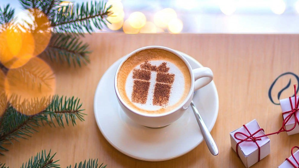 A latte with cinnamon sprinkled in the shape of a gift box on top.