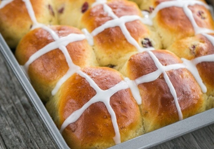 A baking pan full of Hot Cross Buns decorated with icing crosses.